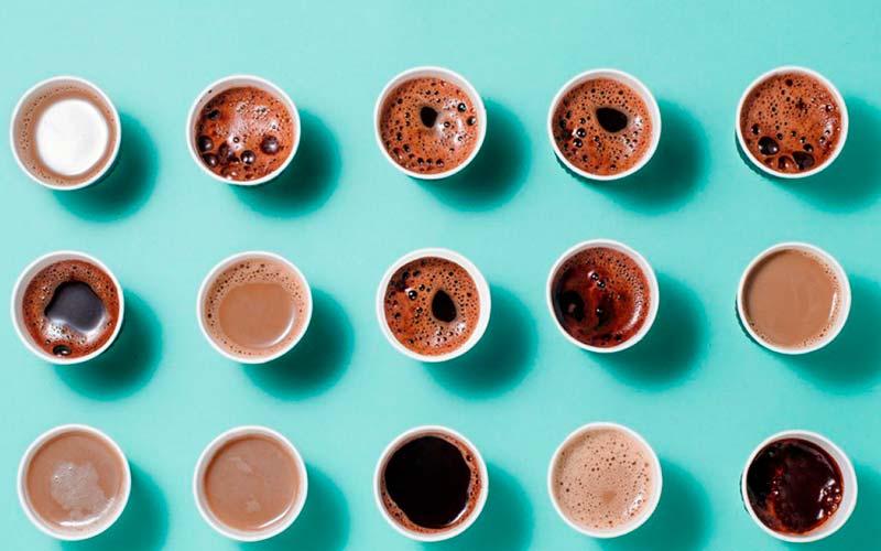 vista aérea de quize xicaras de café com diferentes espumas com fundo azul celeste